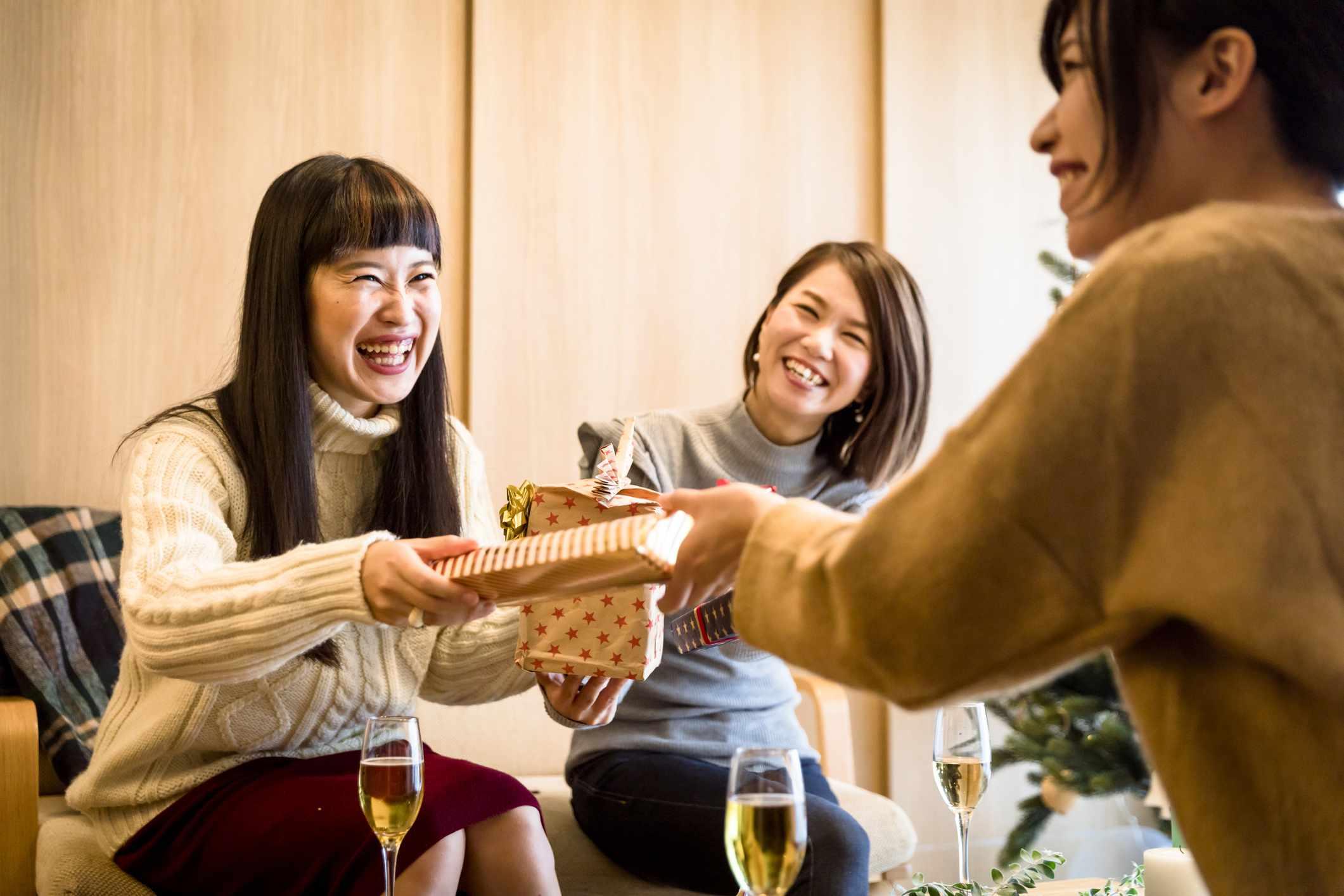 Women smiling, exchange gifts