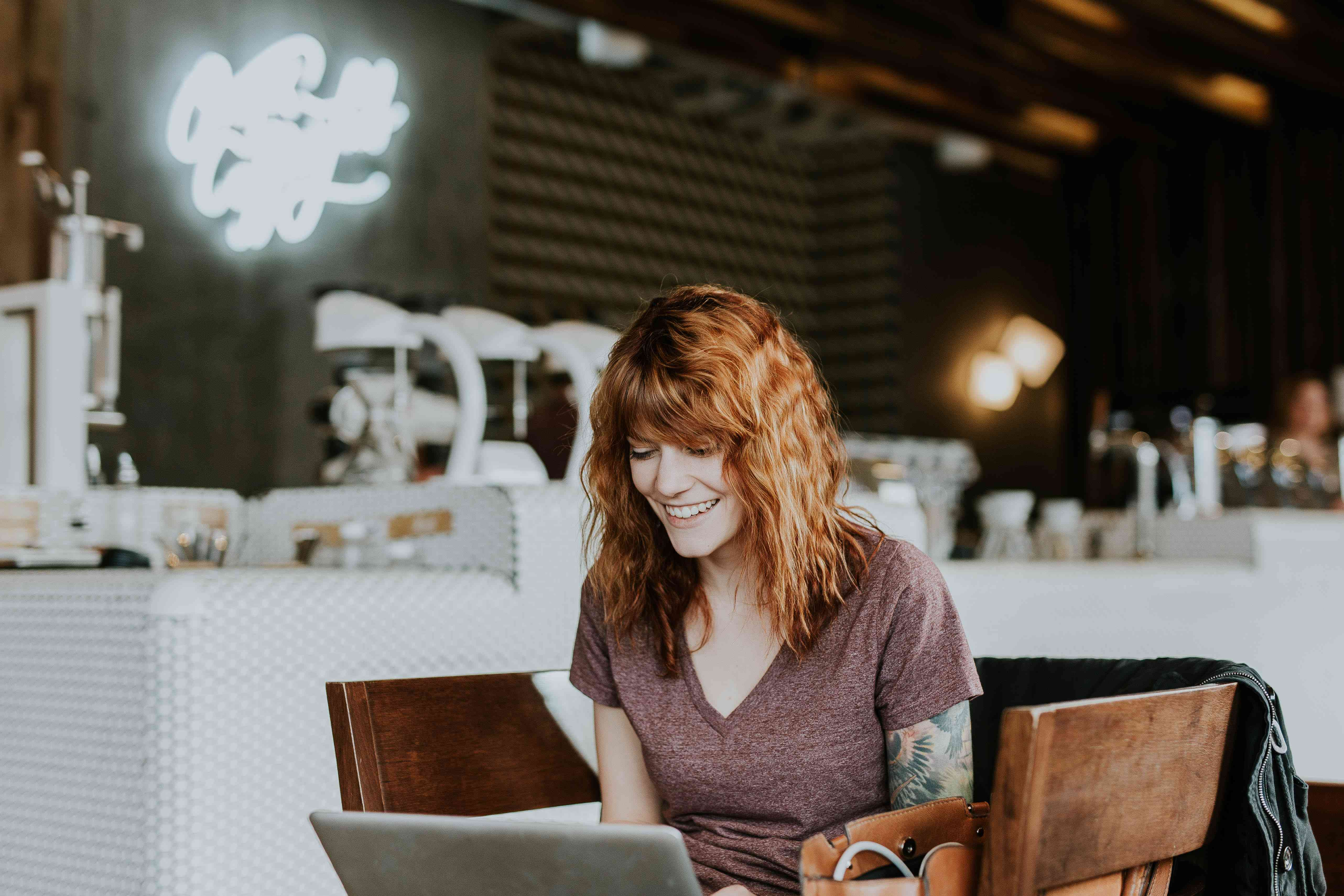 A red-haired smiling woman working on her laptop in a cafe.