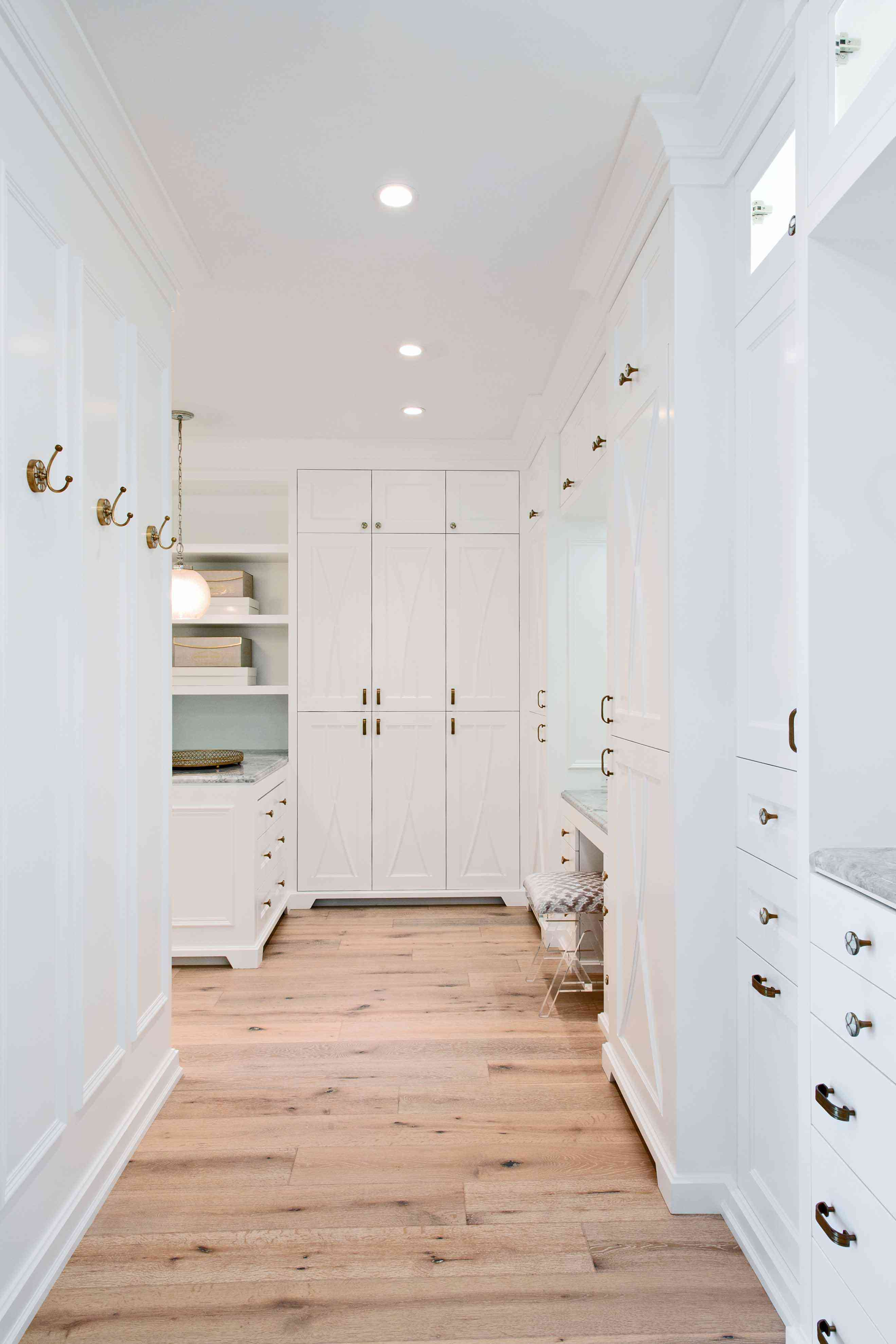 Large walk in closet with plenty of cabinets and drawers.