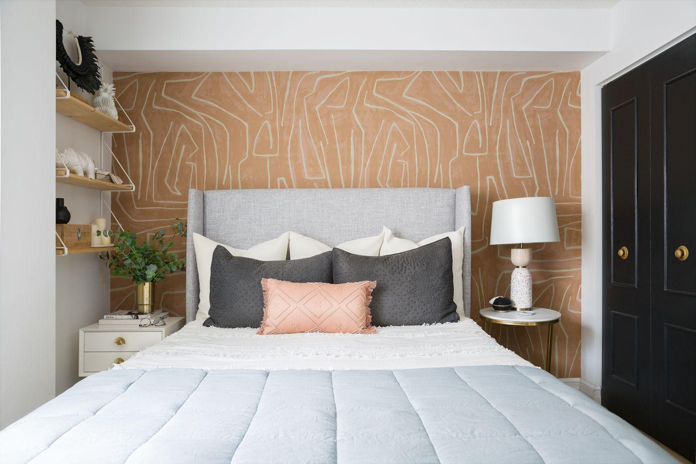 Graphic bedroom with black closet doors.
