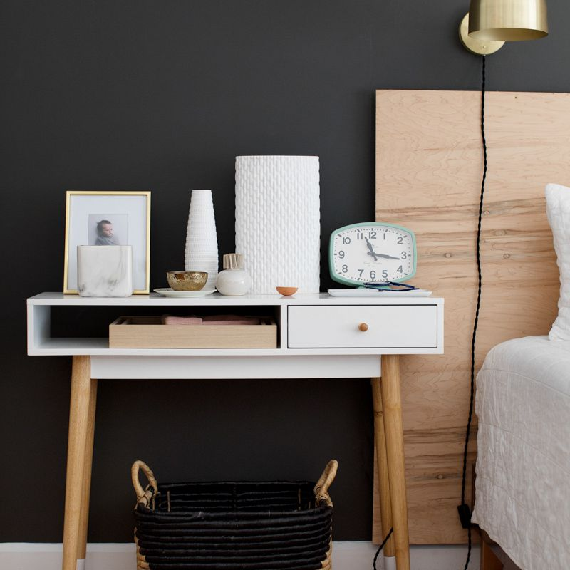 Modern nightstand area with dark charcoal wall and wood and white accents
