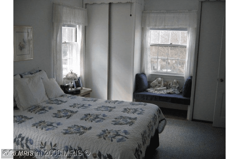 Dingy dark space bedroom with old comforter.