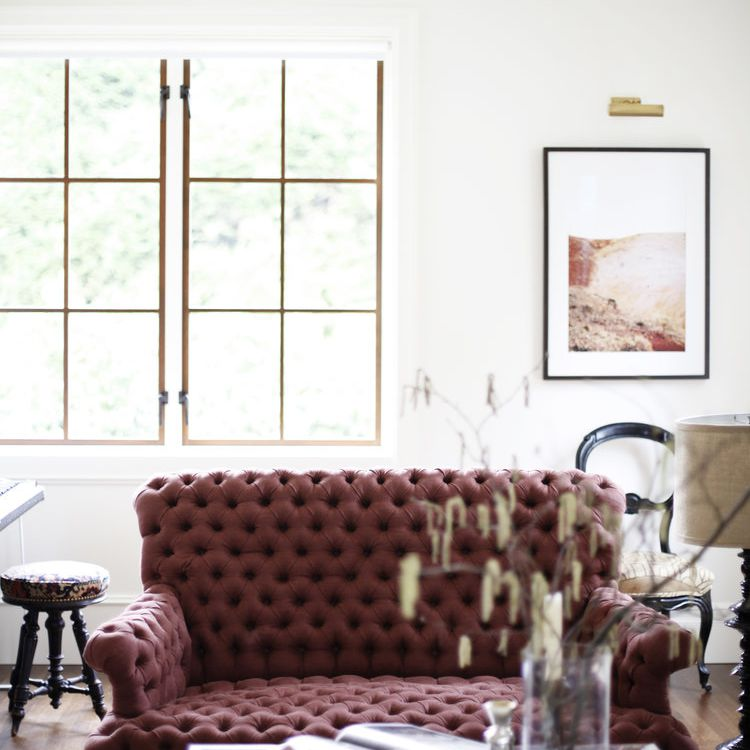 A living room with a burgundy tufted couch in it