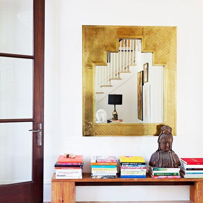La habitación en la casa de Rucker cuenta con libros apilados en un banco de madera con un espejo con marco dorado encima