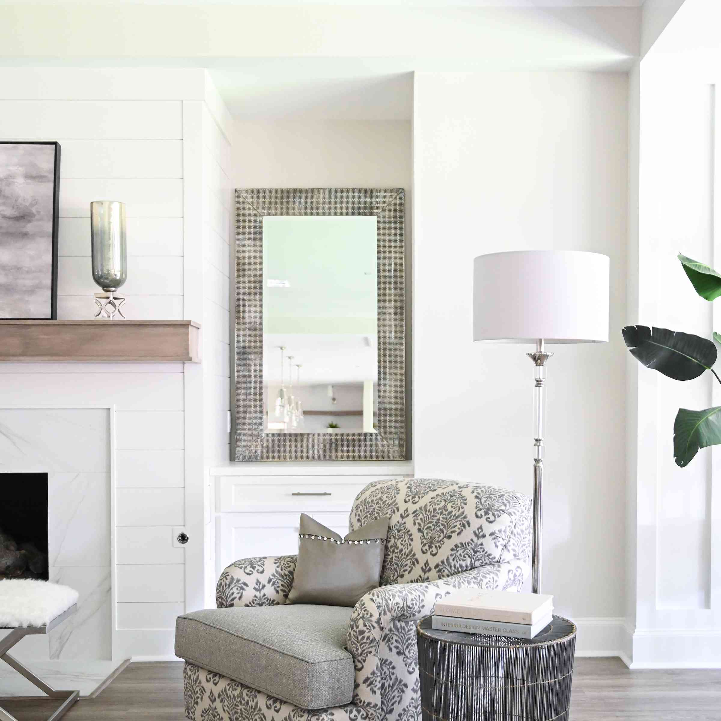 Sitting area with black and white battered chair and silver lamp.