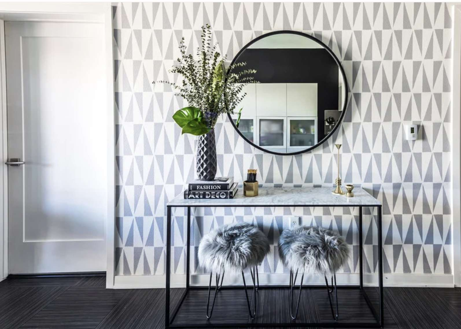 gray and white entryway with triangle pattern wallpaper, large circular mirror above modern style table and gray pouf stools underneath