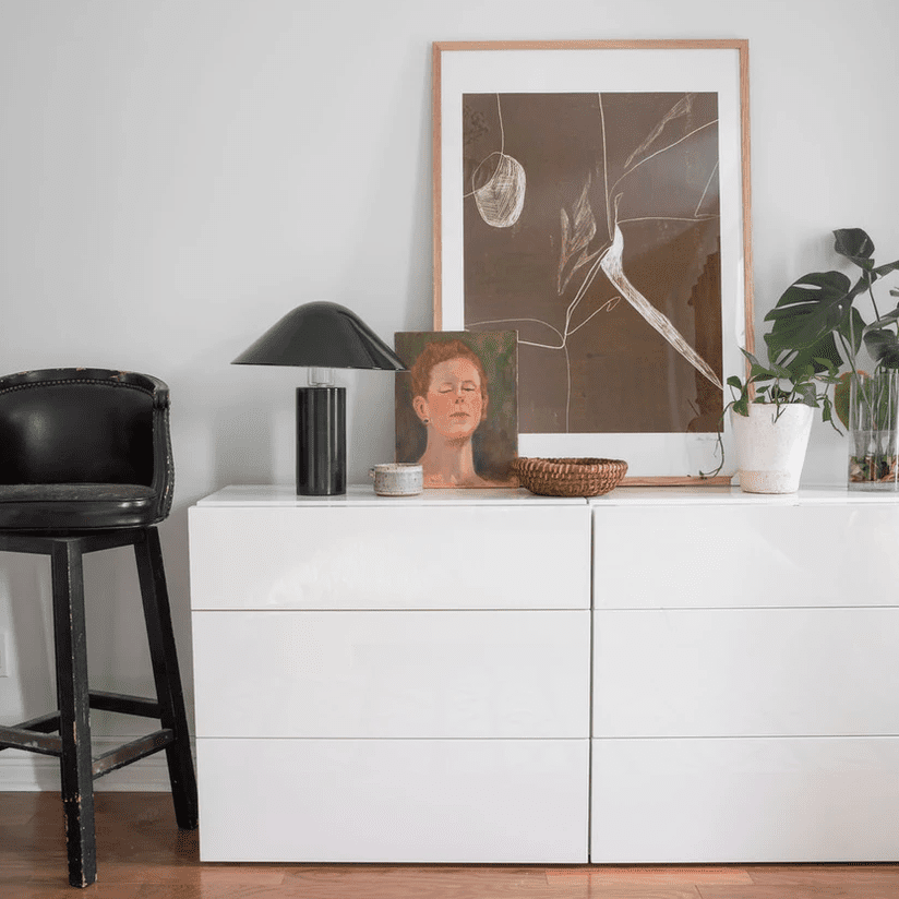 A sleek white dresser topped with a black sculptural table lamp, two works of art, and several plants