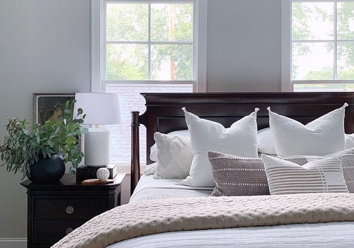 White bed with quilt on top.