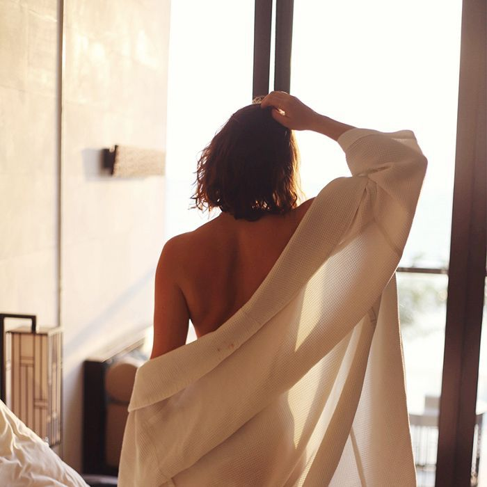 Young woman in robe looks out a window