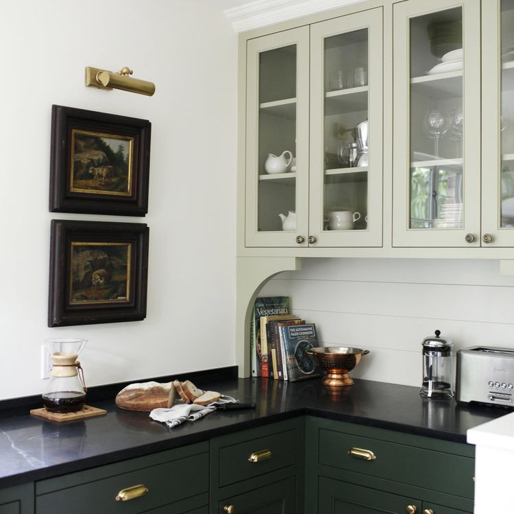 A two-tone kitchen with mint cabinets up top and forest green cabinets down below