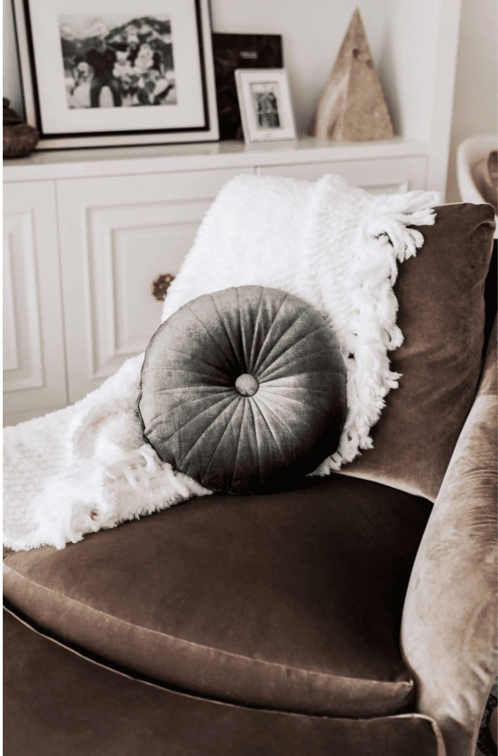 Tufted green velvet pillow on a brown couch