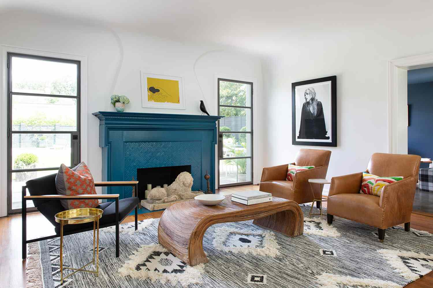 Boho-meets-modern living room with leather chairs, blue mantle and fireplace