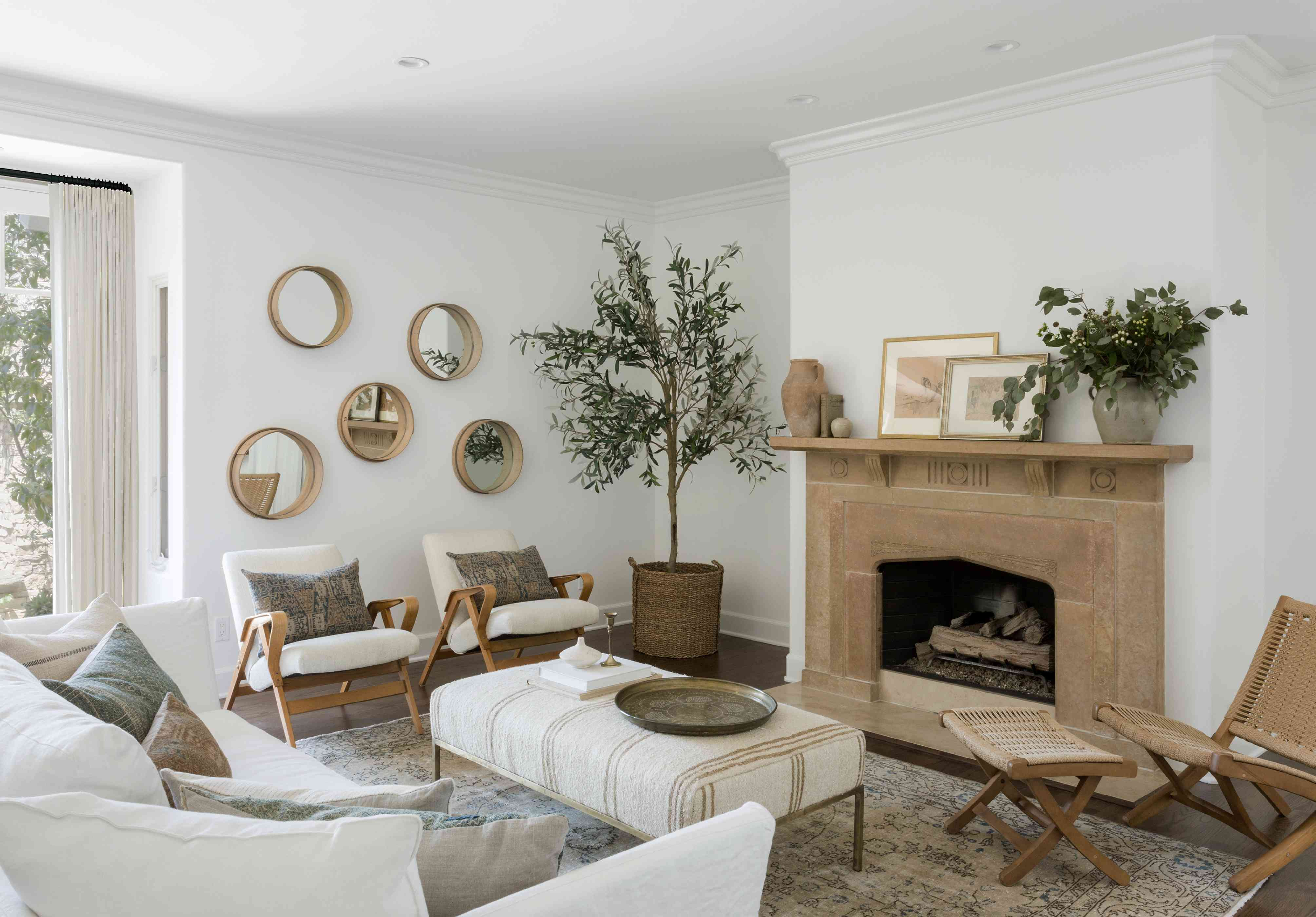 white living room with vintage wicker chair and stool