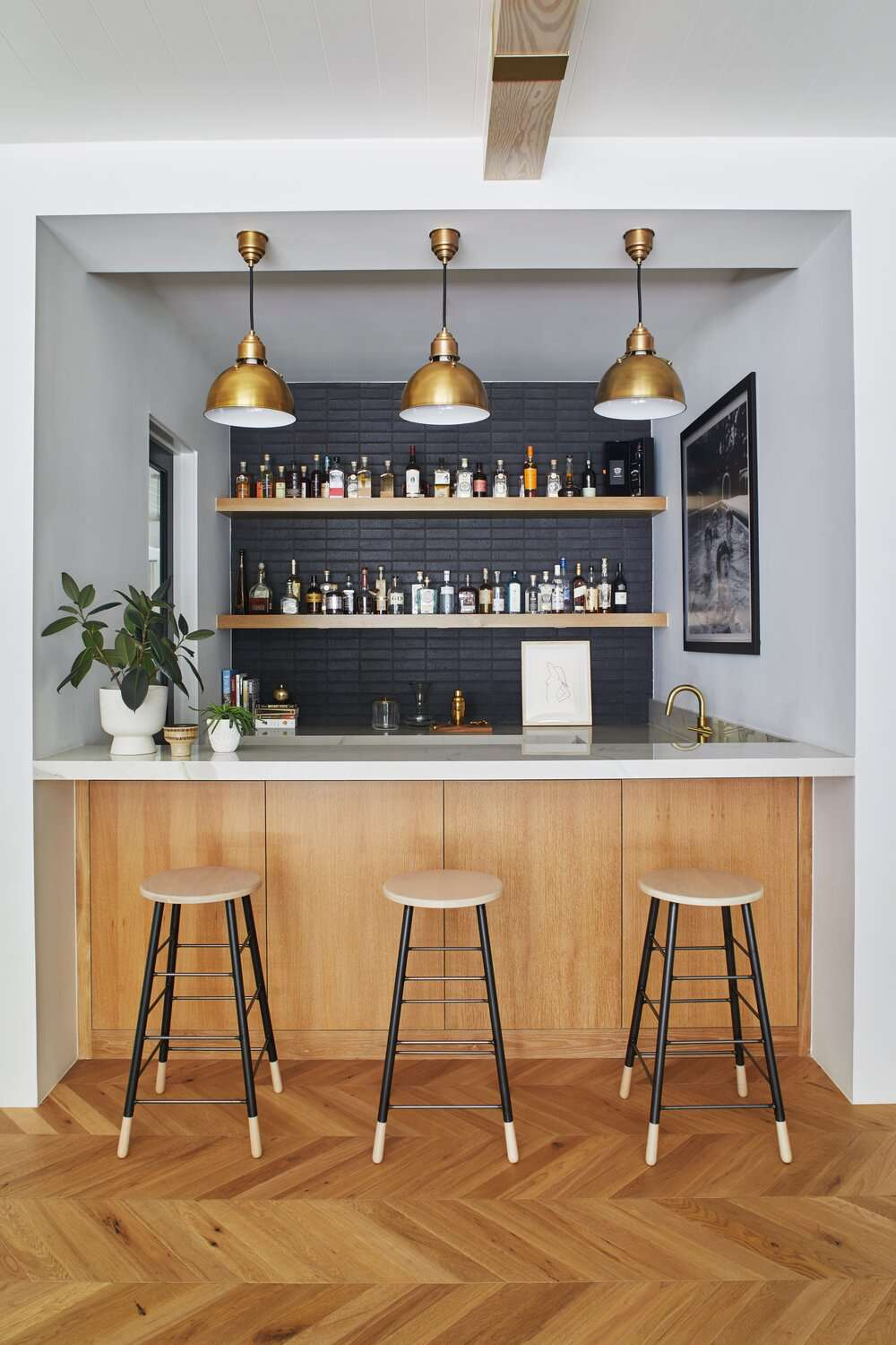 A small kitchen bar with hardwoods laid down in a zigzag pattern