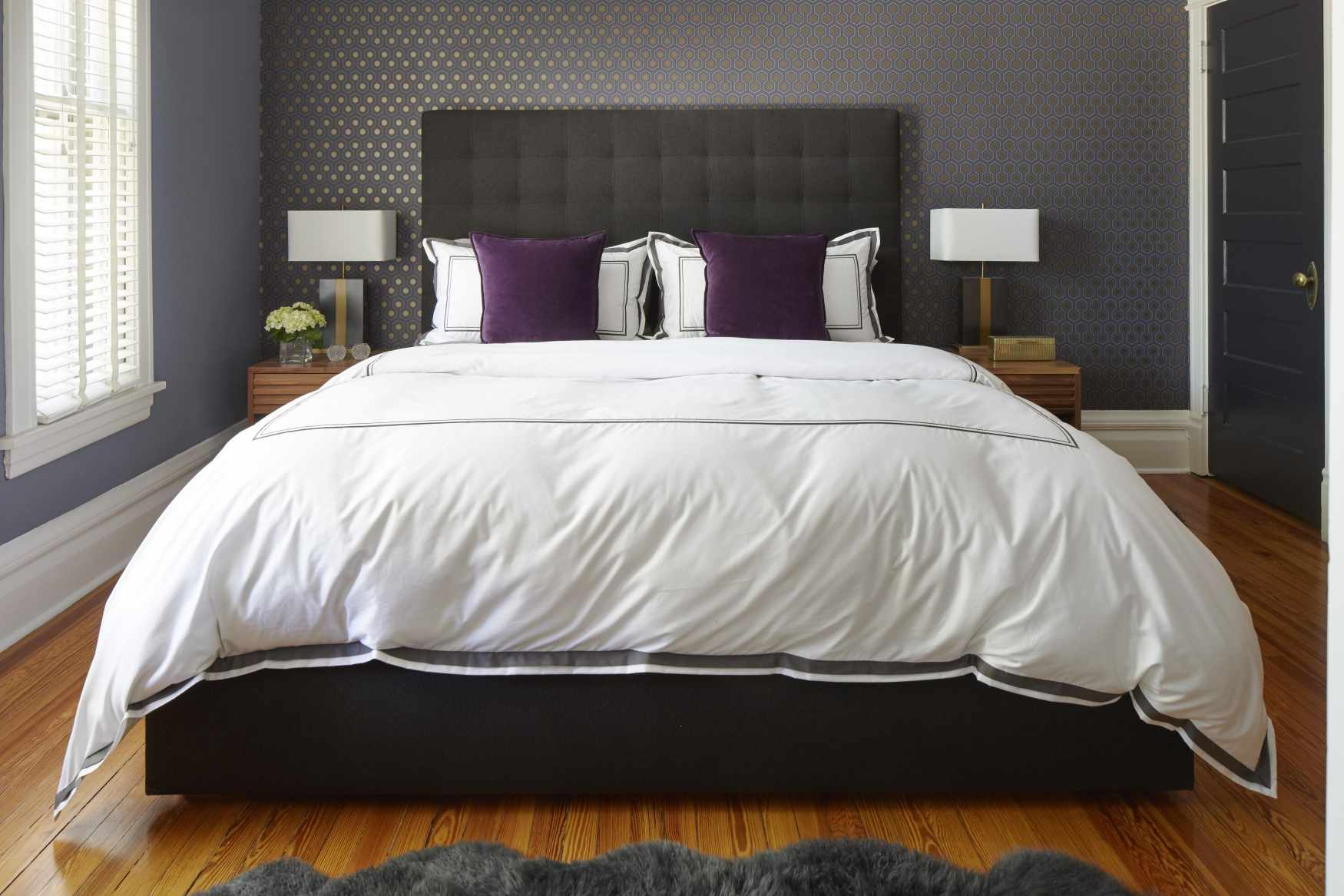 Gray bedroom with purple pillows