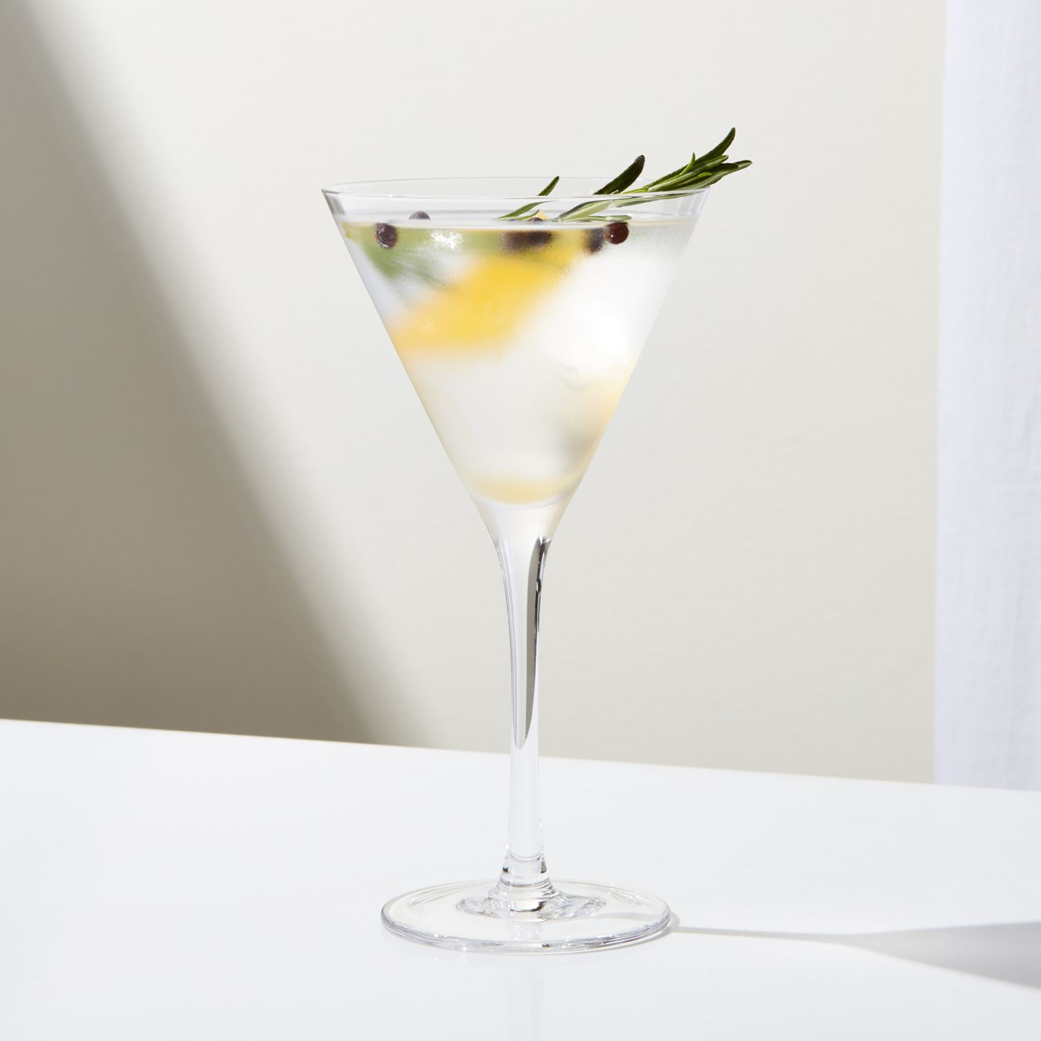 A cocktail glass filled with water, lemon, berries, and a rosemary sprig.