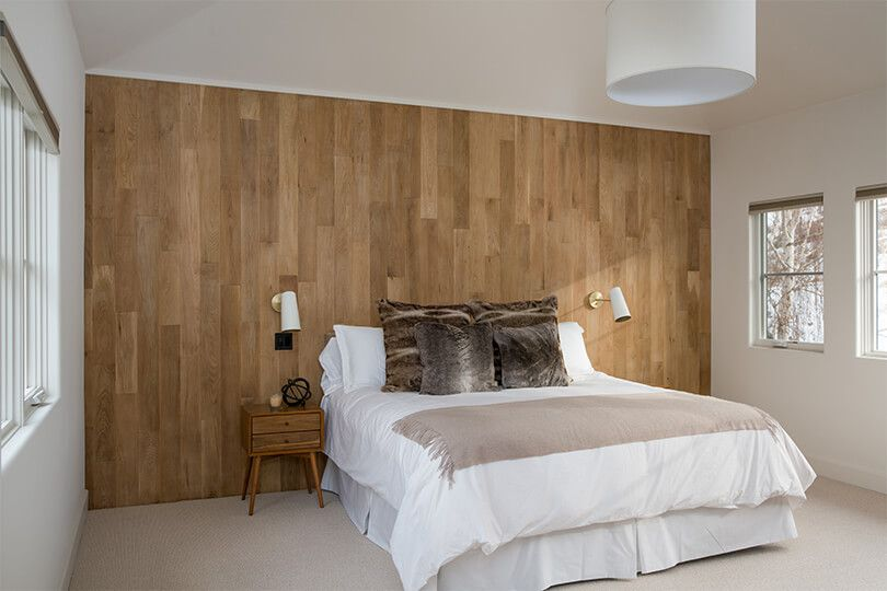 A bedroom with wood-paneled walls and faux fur pillows