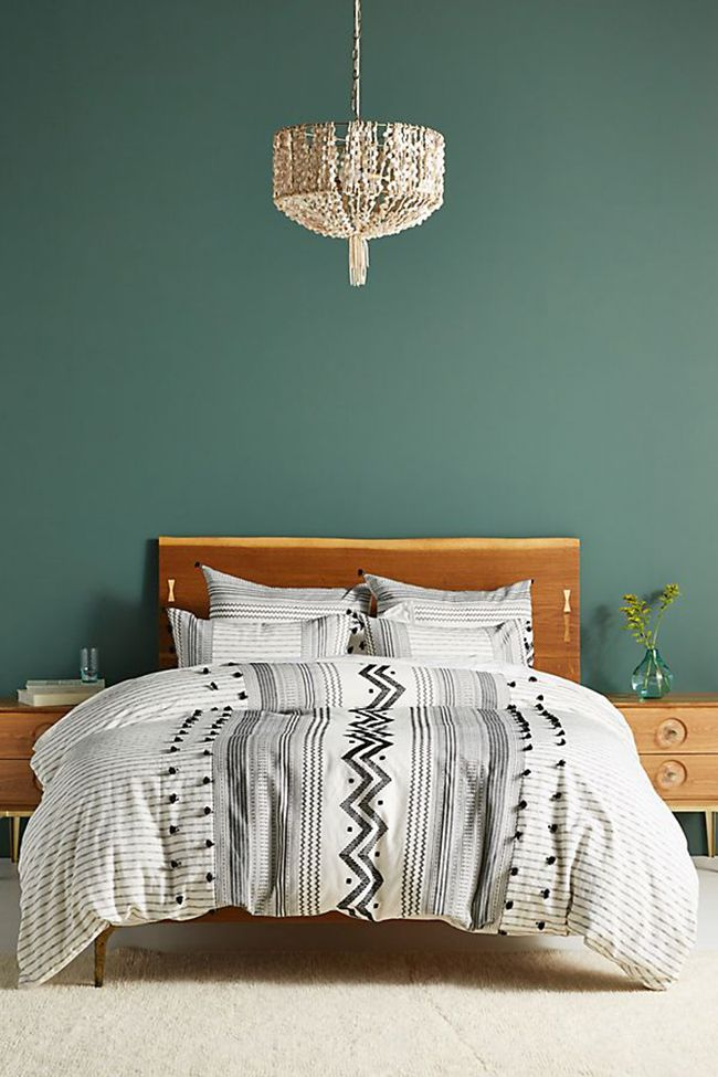 Bedroom with dark green wall, warm wood bedframe and black-and-white embellished bedding.