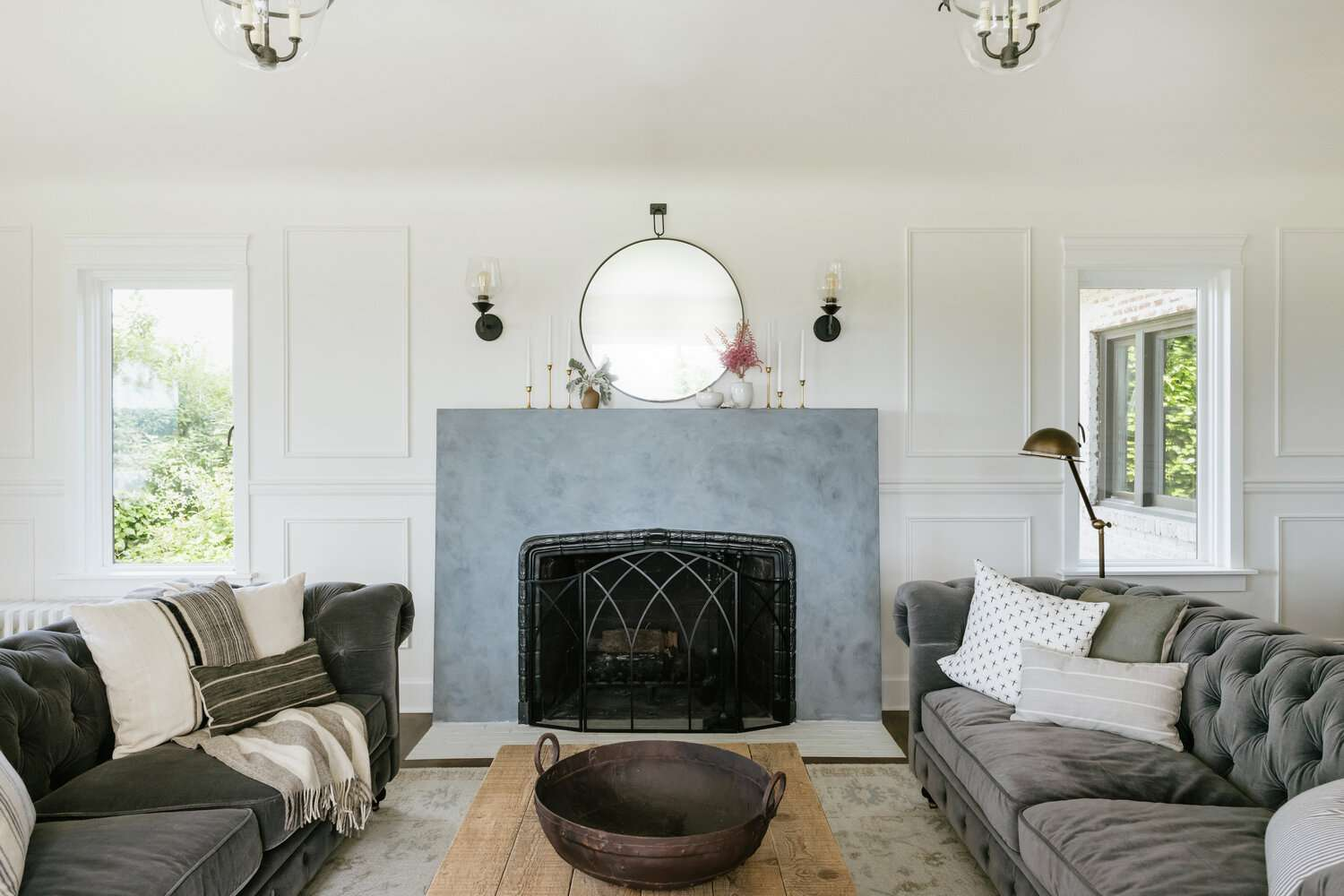 A living room with a gray fireplace and two slate gray couches