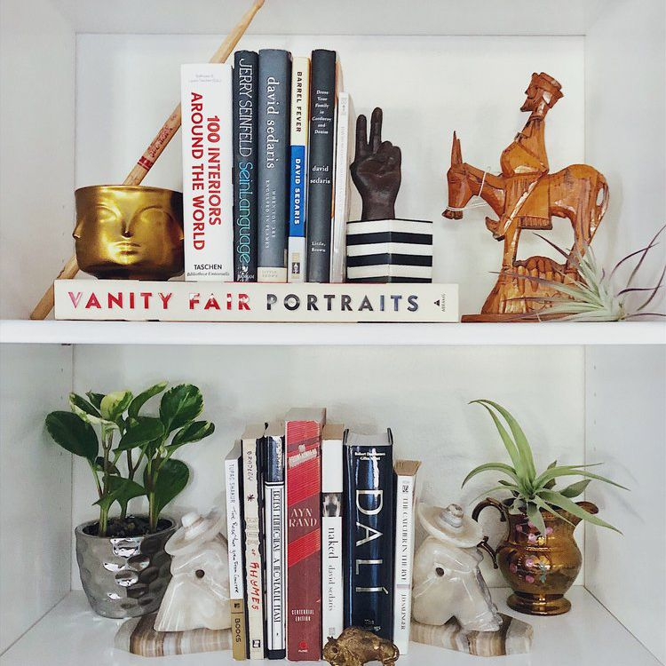 An eclectic bookshelf scene containing interesting odd-numbered groupings of decorative objects.