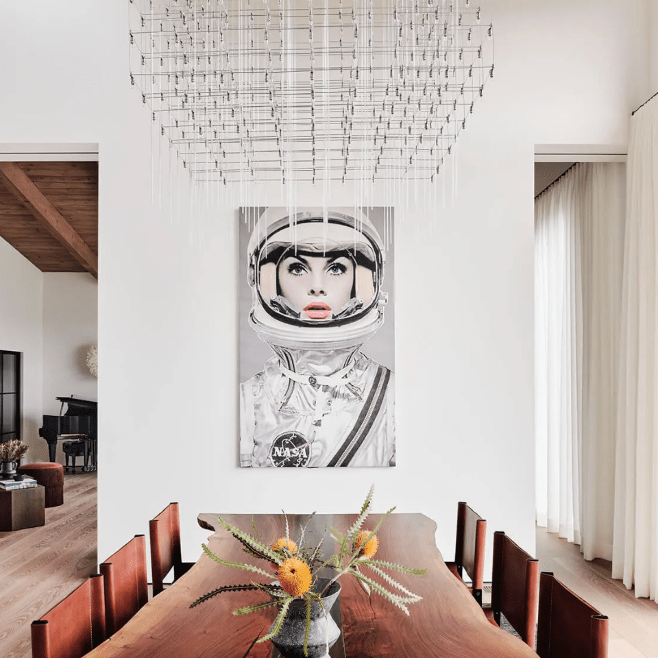 A dining room with a rustic table and a contemporary light fixture