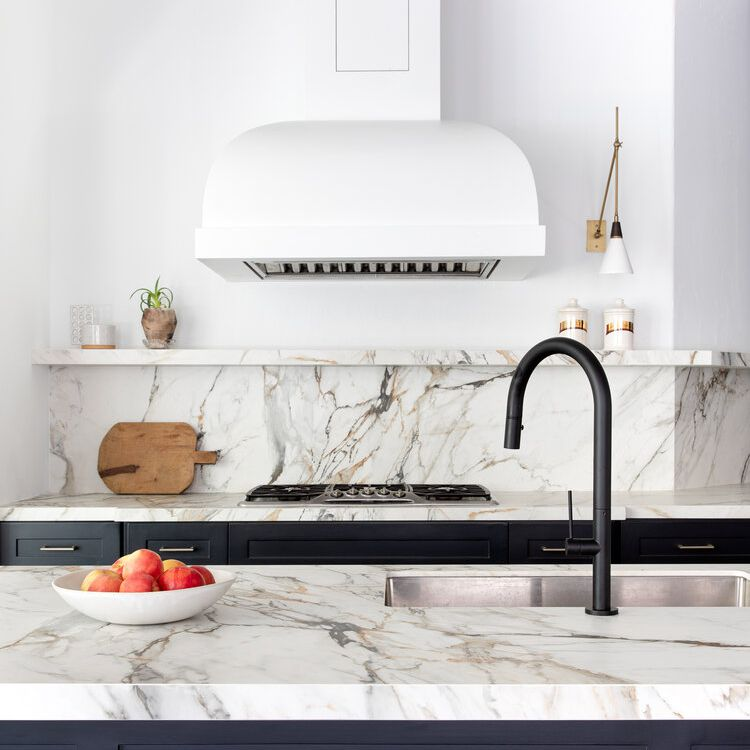 A kitchen with navy cabinets, marble countertops, and a marble-lined backsplash