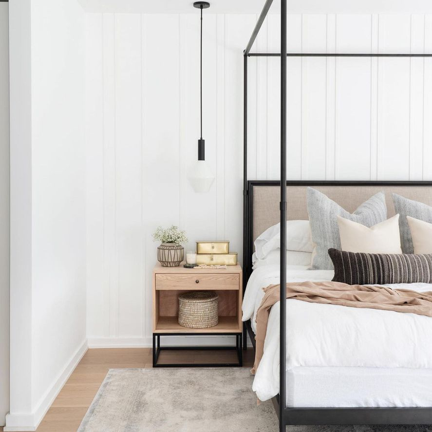 Light bedroom with asymmetrical wood paneling