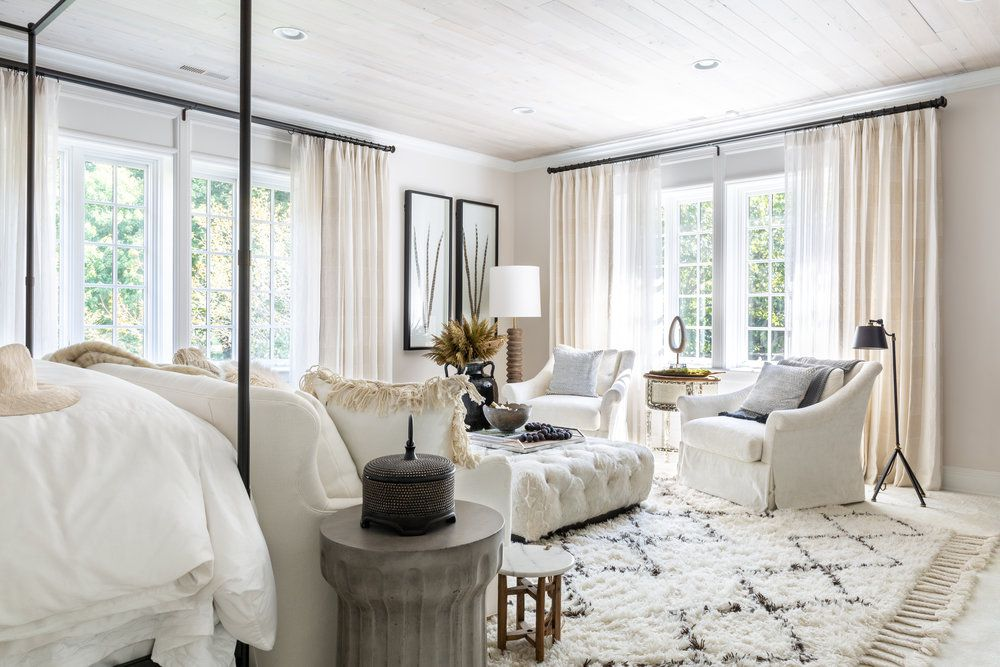 A large white bedroom with cream colored drapes