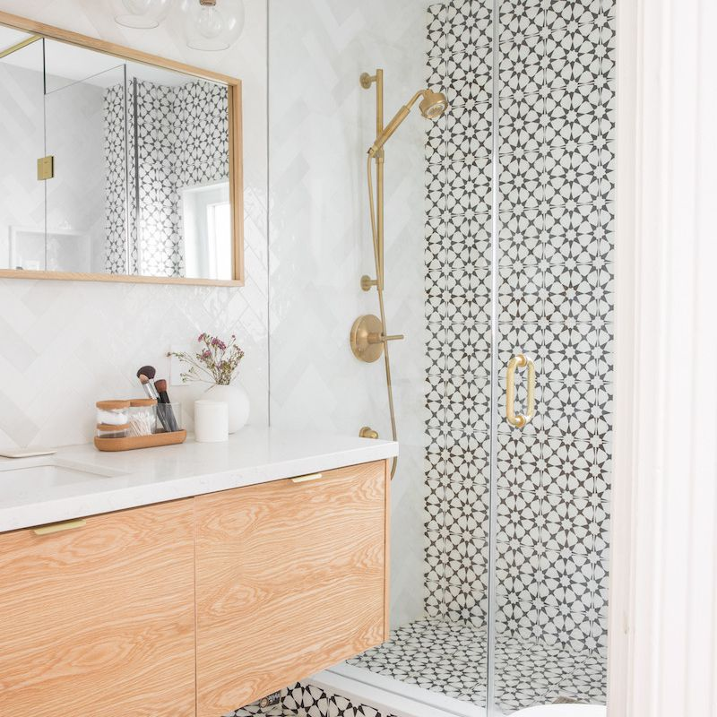 Modern bathroom with light wood vanity, graphic tile treatment, and gold accents