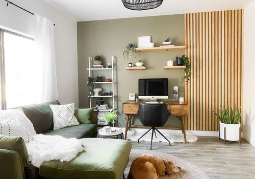 A living room with an office nook that has a wood feature on the wall and open storage.