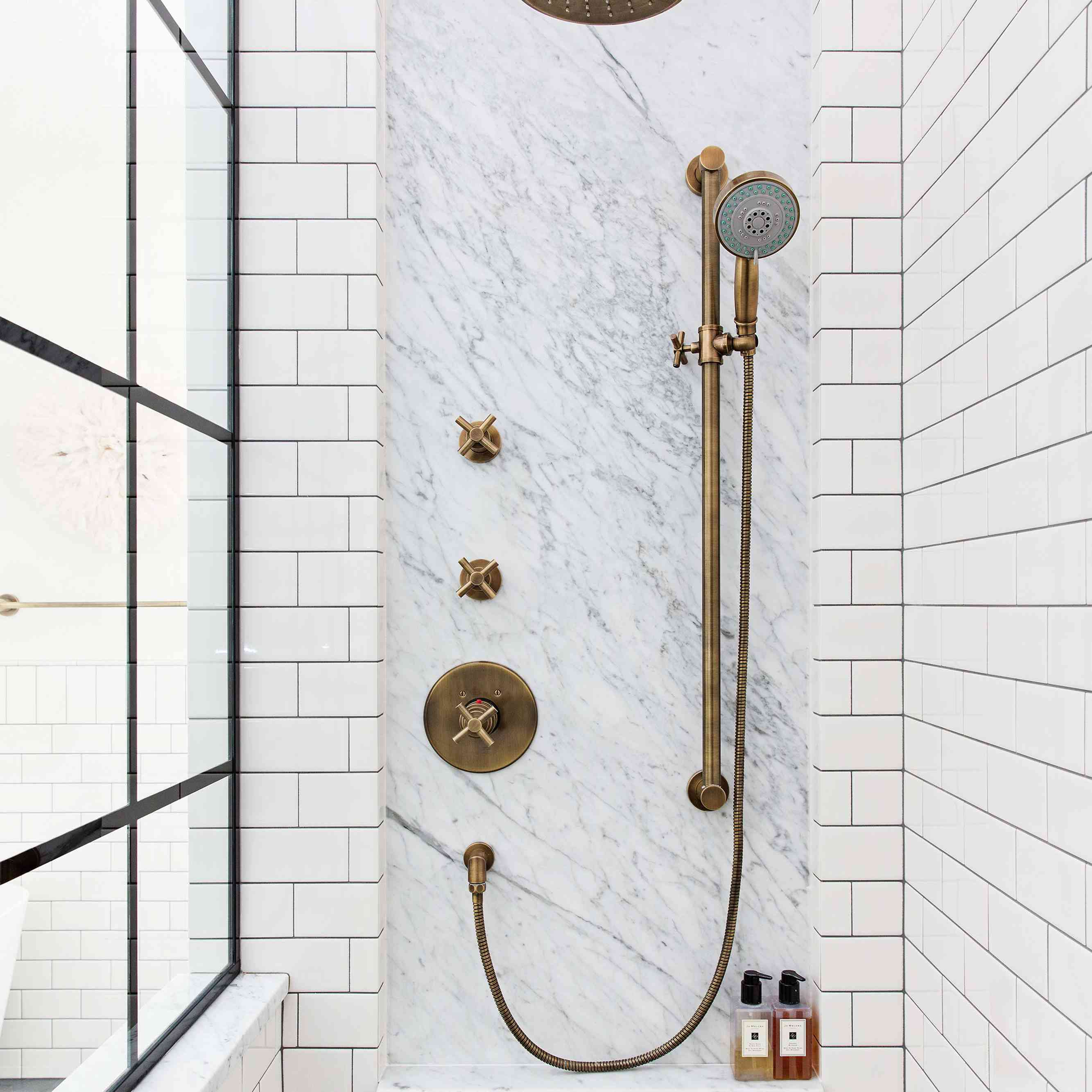 A white tile-lined shower with pops of textured marble
