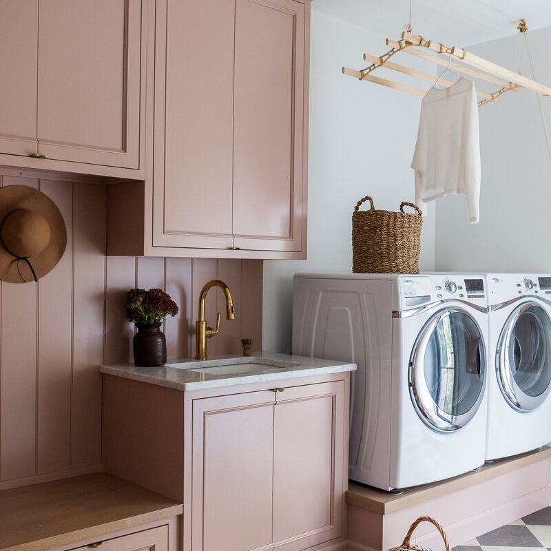 Pink laundry room with faux flowers.