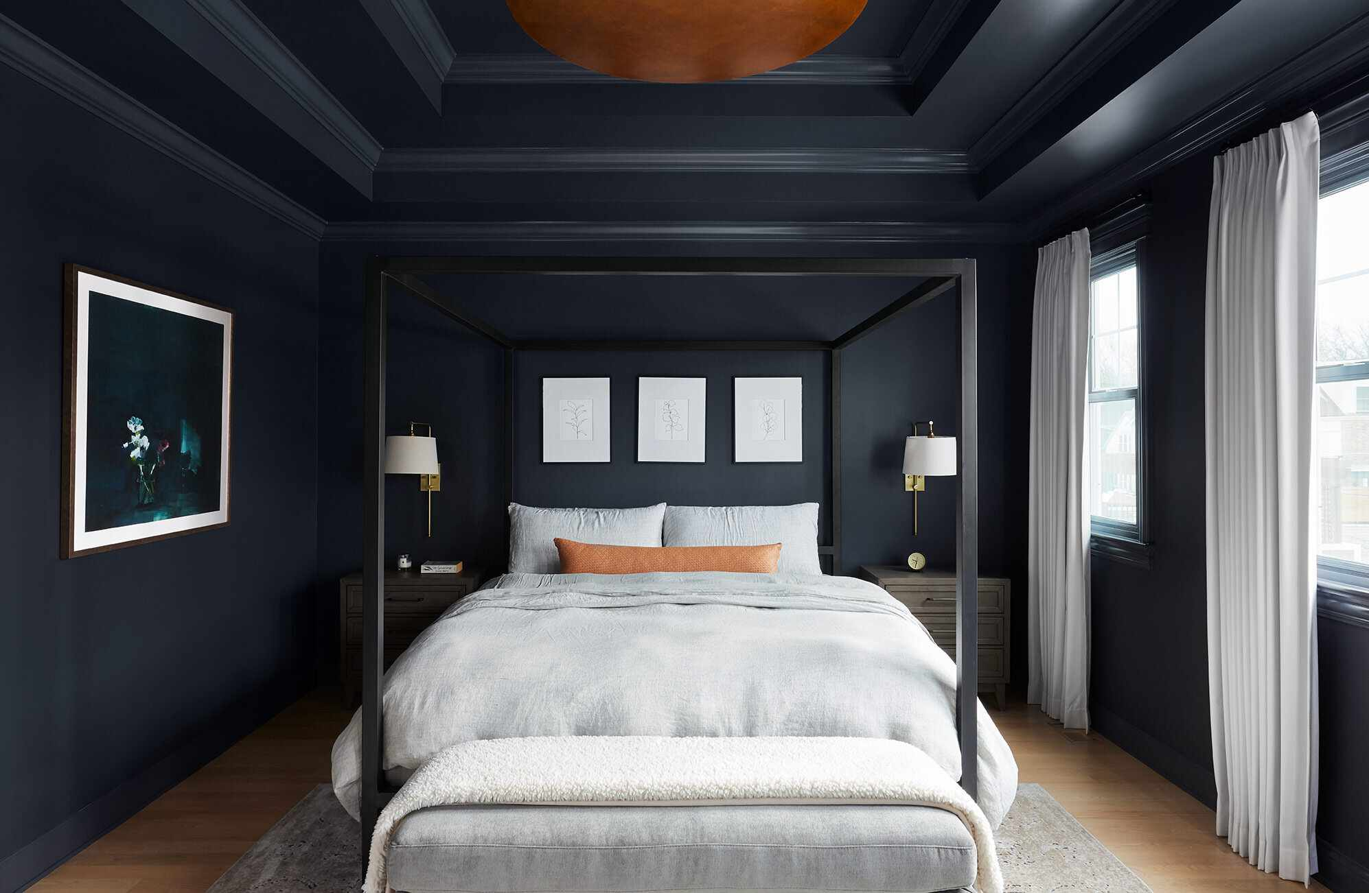 A navy bedroom with white drapes