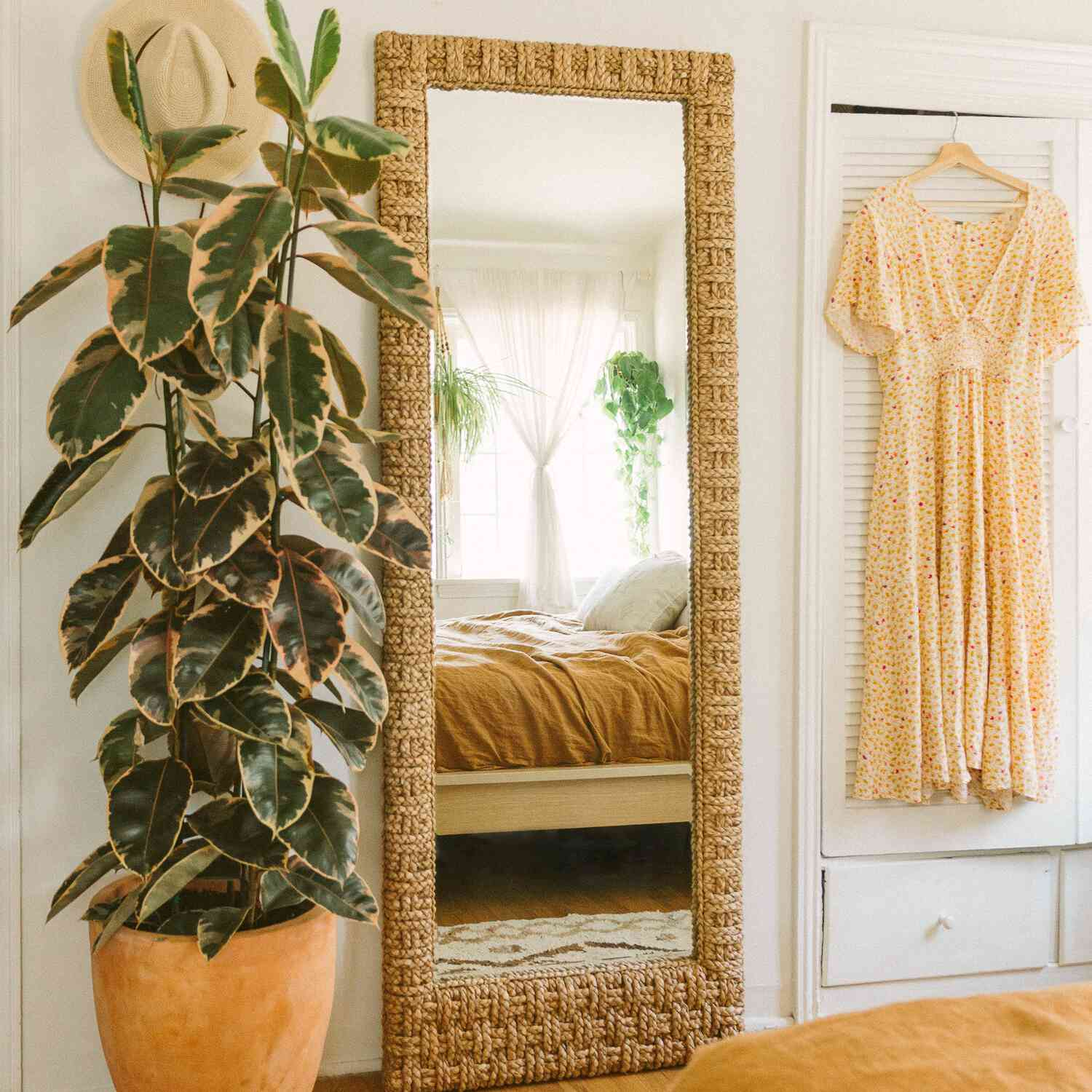 Tall rubber tree next to a standing mirror in a boho bedroom