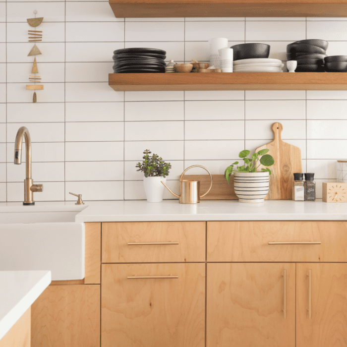 A kitchen with light wood cabinetry and shelves