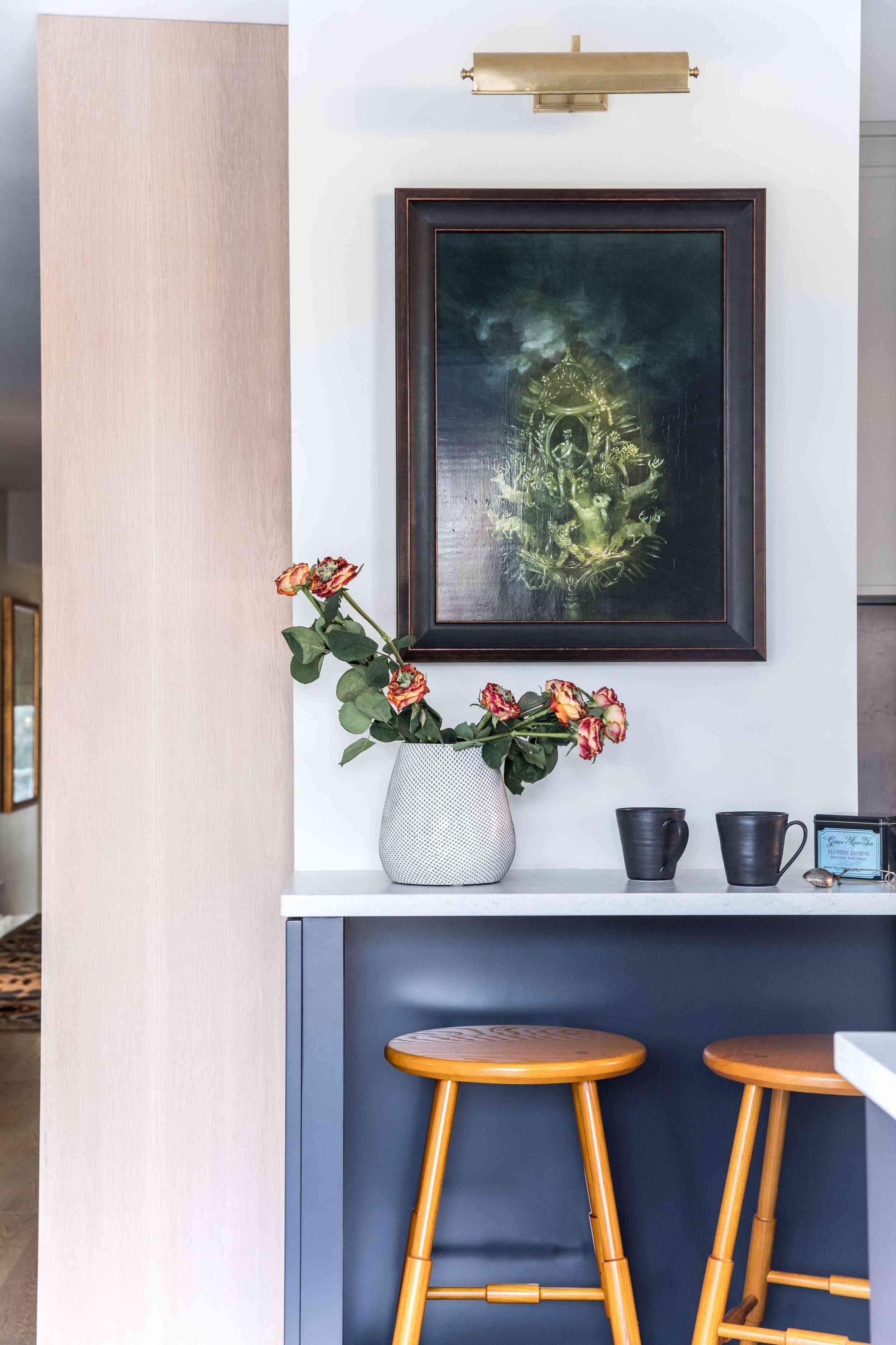 A rustic kitchen with a painting, flowers, and several wooden stools