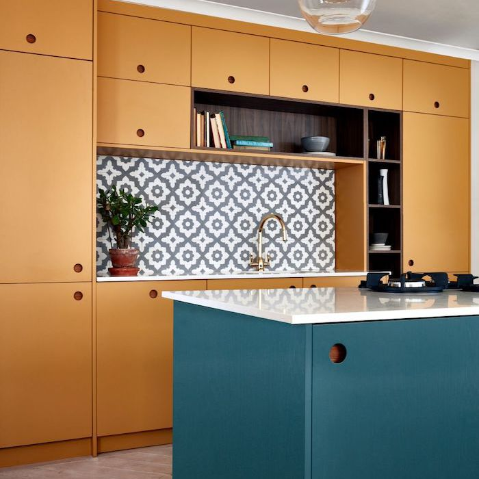 blue and brown kitchen cabinets with teardrop light fixture