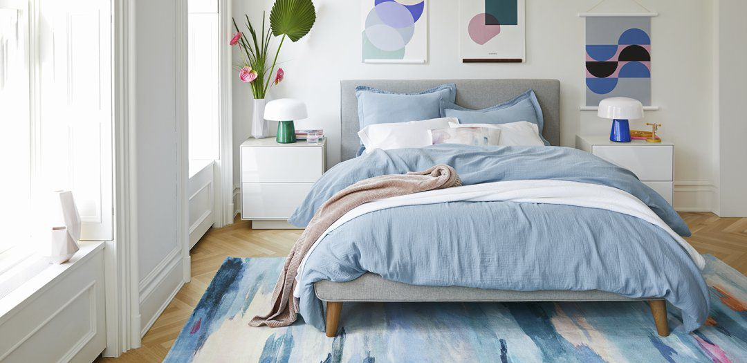Gray headboard supports blue bedding and blue patterned carpet