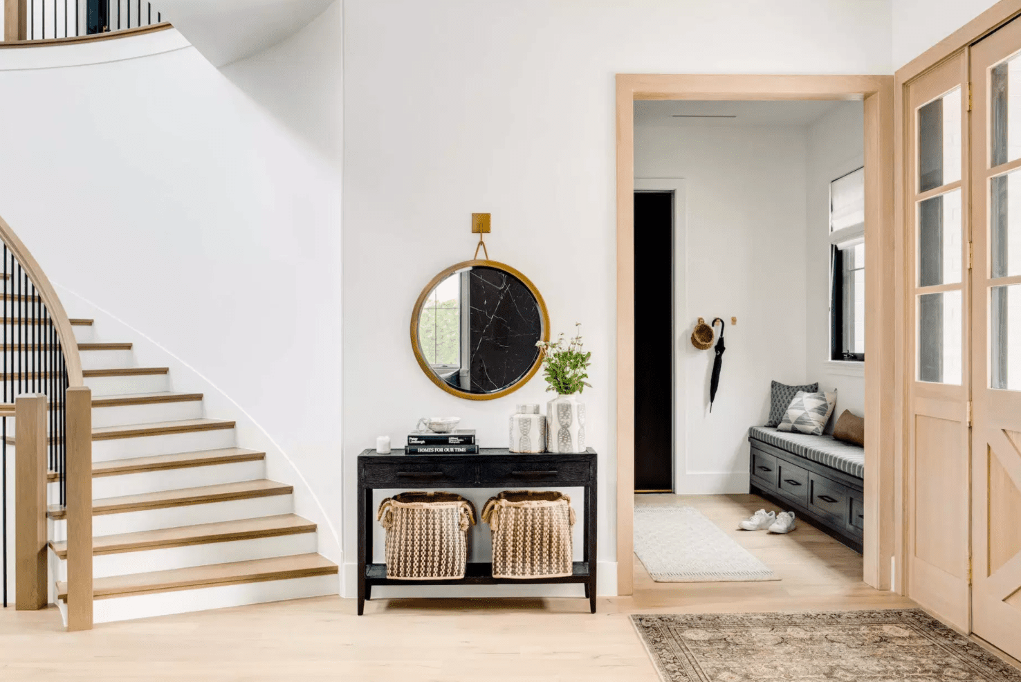 An entryway with a small black console table, a small circular mirror, and two woven baskets