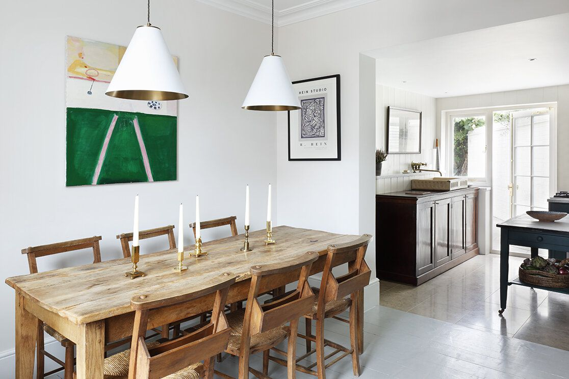 A dining room with rustic furniture and sleek white pendant lights