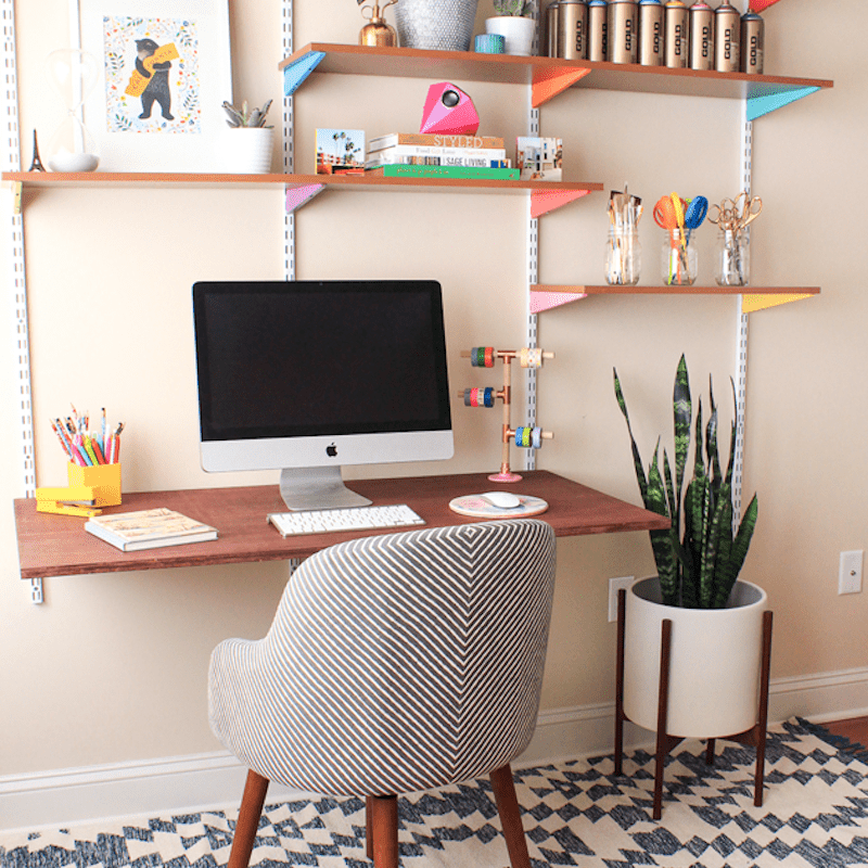 A desk lined with colorful craft supplies