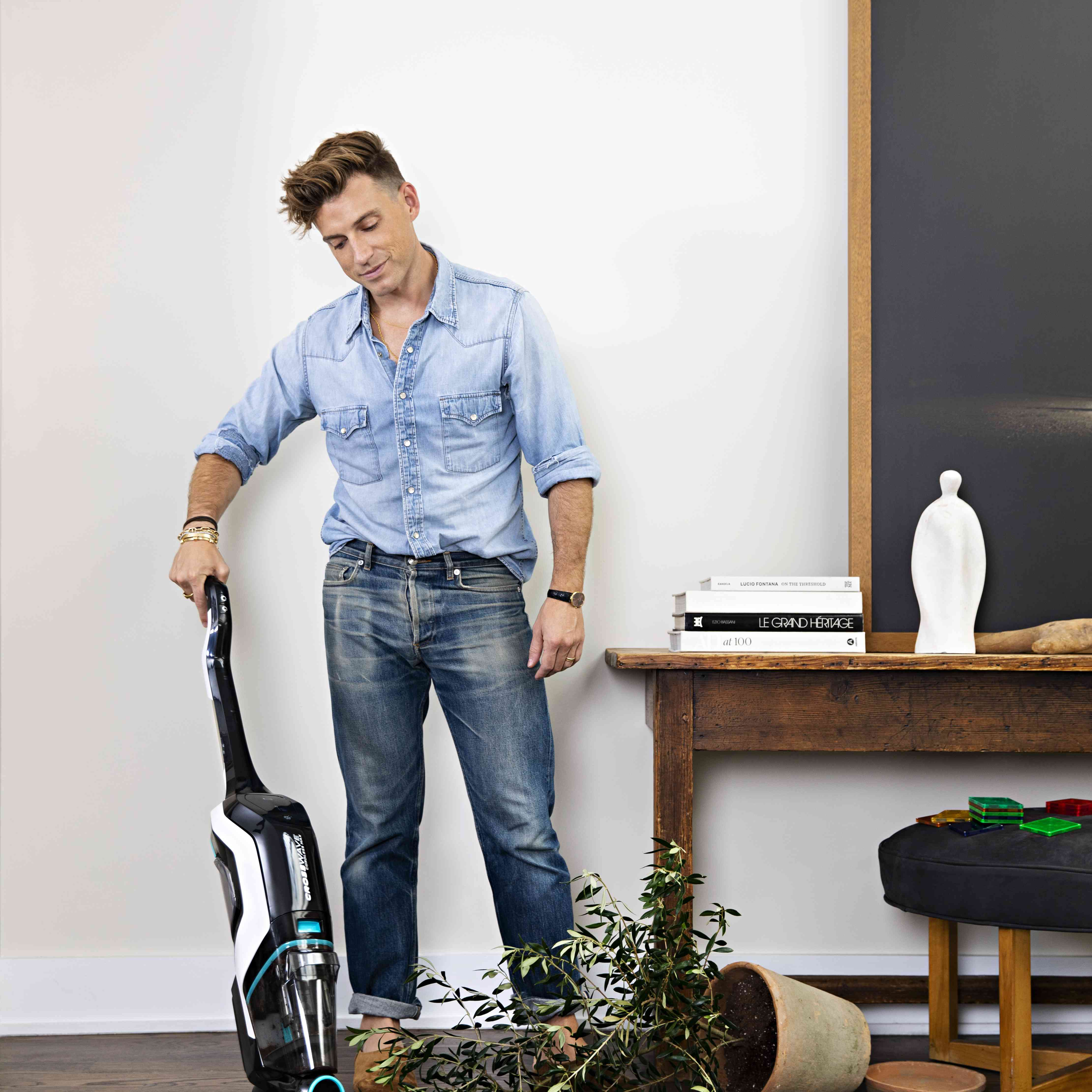 Jeremiah Brent using the BISSELL CrossWave Cordless Max to clean up after a spilled potted plant