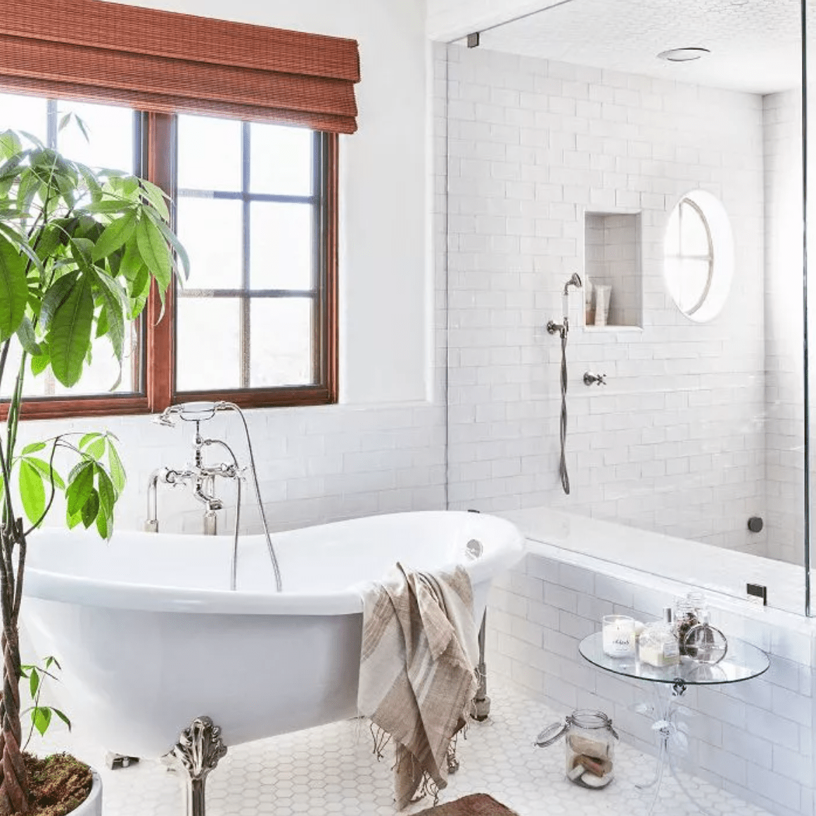 Tiled bathroom with woven window treatments and potted tree