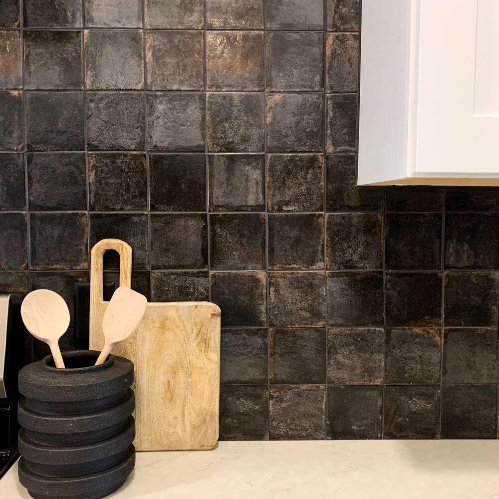 A kitchen with a black tiled backsplash