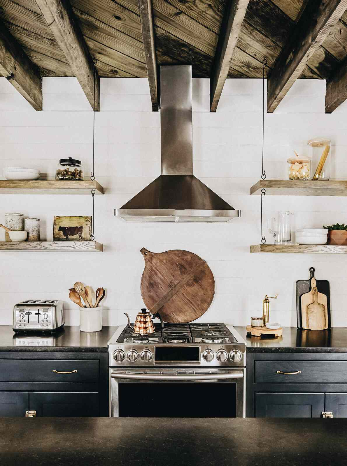 A rustic kitchen with a wood-lined ceiling and several hanging wooden shelves