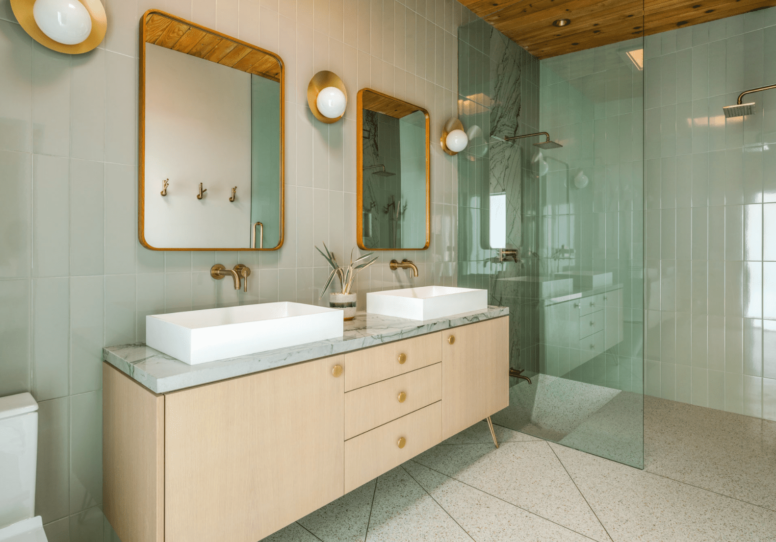 A bathroom lined with wall-to-wall sage green tiles