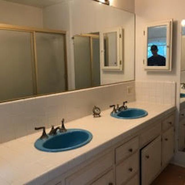 Before shot of bathroom with bright blue sinks.