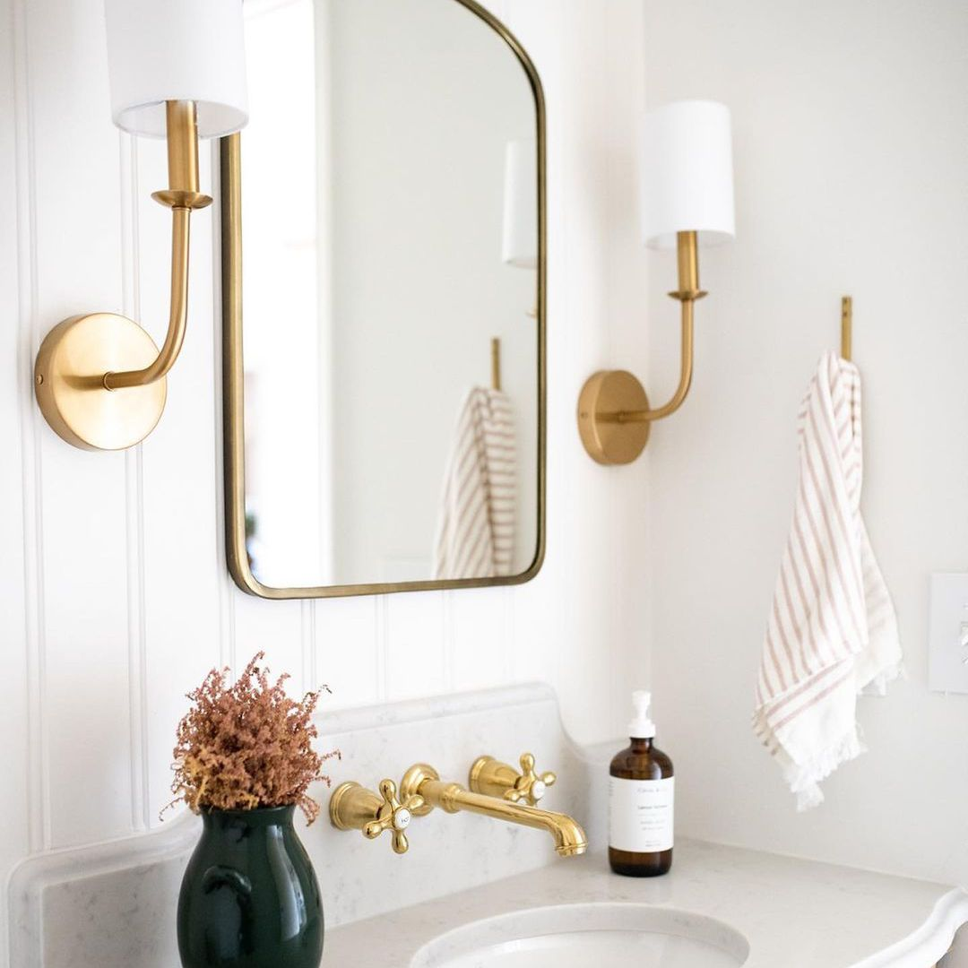 White beadboard bathroom with gold accents.