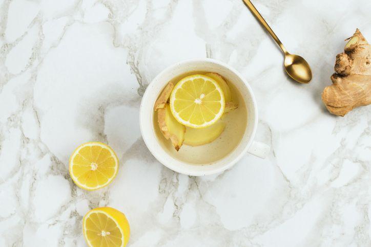 Flatlay de bebida saludable con limón y raíz de jengibre fresco sobre fondo de mármol