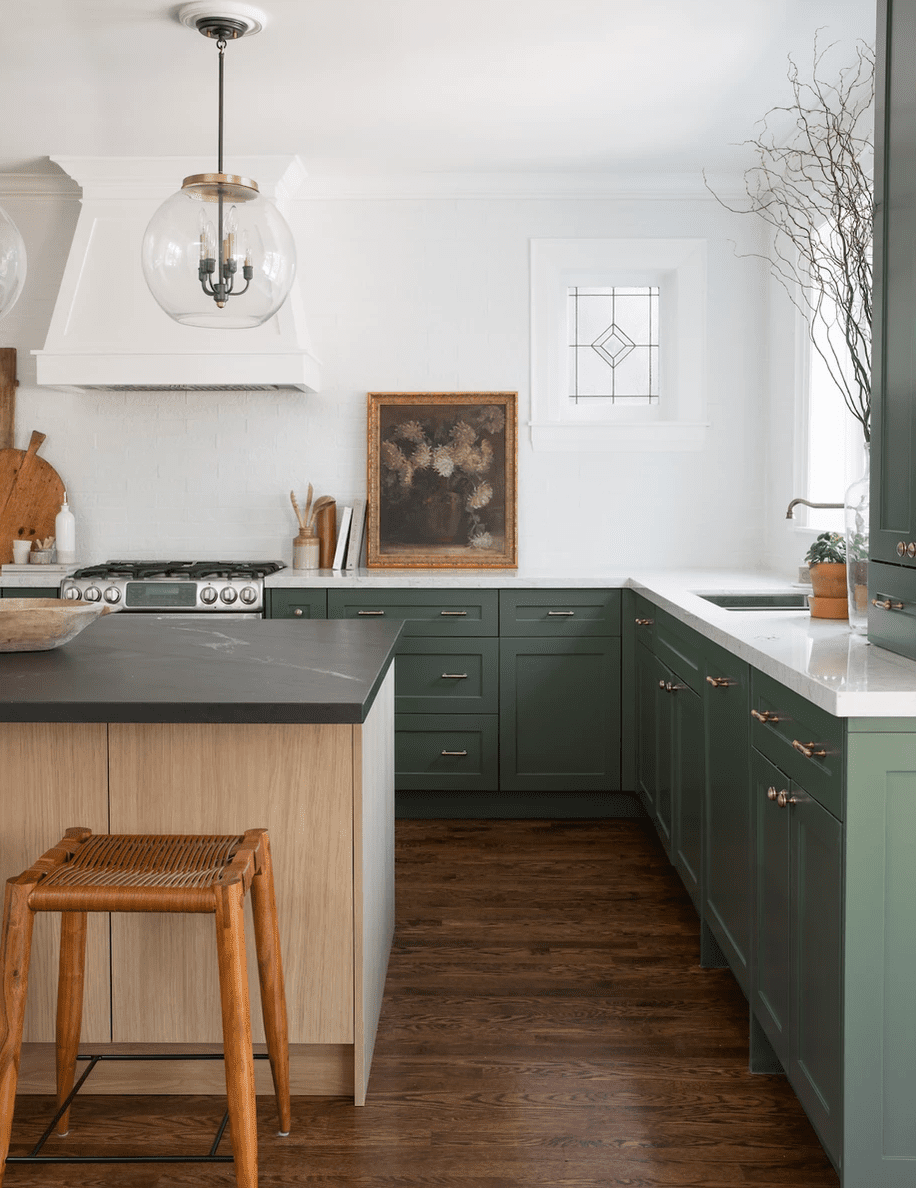A kitchen with green cabinets and dark hardwood floors